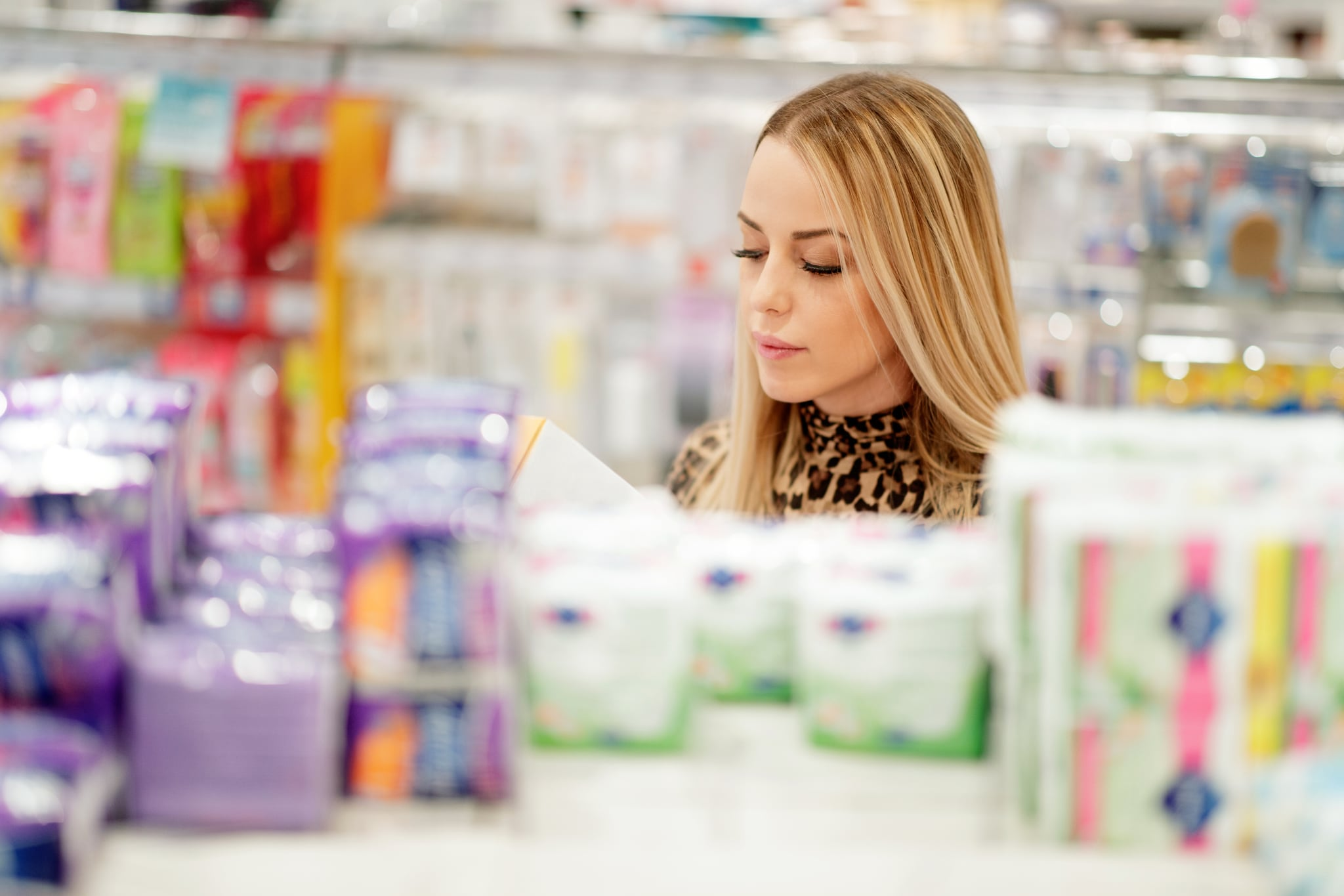 Blonde woman shopping in pharmacy, copy space