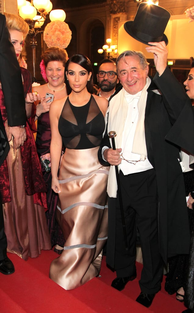 "While Kanye West was hitting up fashion shows in Paris, Kim Kardashian traveled to Austria to take part in the annual Vienna Ball on Thursday. Kim, along with her mother, Kris Jenner, was at the ball as a guest of Austrian businessman Richard Lugner, who has a history of bringing sexy stars to the ball. (He previously brought Paris Hilton, Pamela Anderson, and Carmen Electra.) Kim was reportedly paid $500,000 for the appearance, but Richard was allegedly unhappy with his date, complaining that she wouldn't dance with him and that she was being ""annoying."" The businessman reportedly said in a press conference about his date that Kim was busy filming and that he thought that ""she should be with (him) and not anywhere else that is not agreed upon."" And this was all before the ball even started. According to TMZ, there is a good reason behind Kim's less-than-excited demeanor at the ball, as some sort of Austrian celebrity named Chris Stephan greeted Kim in full blackface and a white tuxedo and tried to pretend he was Kanye. As if that's not bad enough, another guest approached her to dance and used the N-word when saying he wanted to dance to her while the orchestra was playing ""N*gg*s in Paris."" Yikes. On Friday, Chris issued an apology on his Facebook page, saying, through translation, that he wanted to ""apologize to those who felt under attack."" TMZ's report also claimed that Kim complained about Richard, saying he would inappropriately and aggressively grab her and kept asking her to ditch her security team so that they could be alone. Kim allegedly left the ball early after staying for an hour and a half. Despite all the reports, we will soon find out what really went down as everything was reportedly captured by the cameras for Keeping Up With the Kardashians."