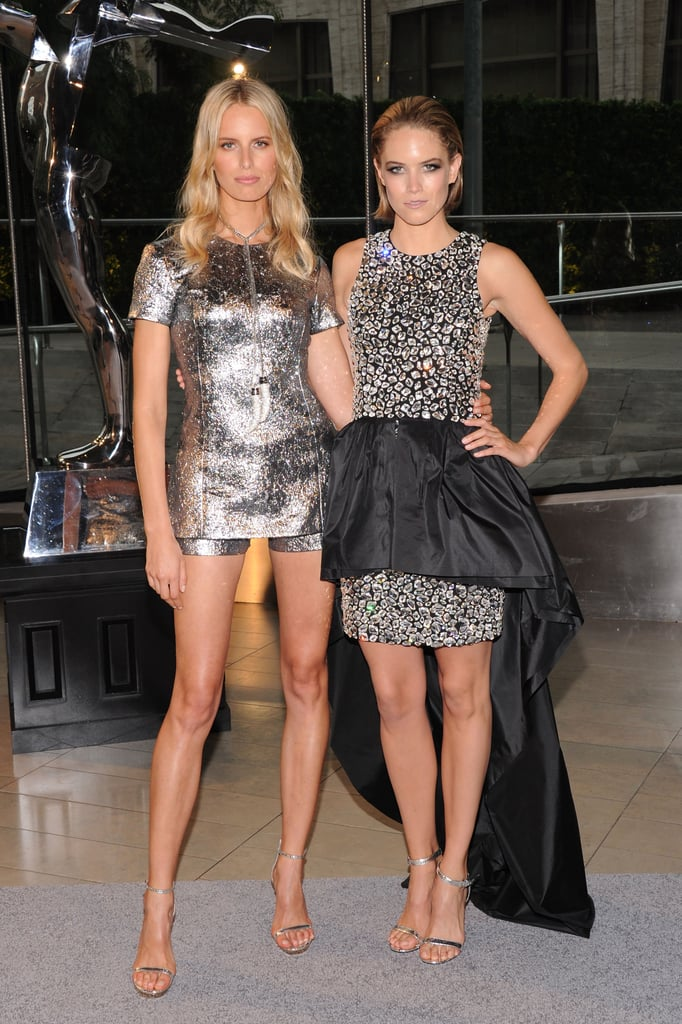 Karolina Kurkova and Cody Horn coordinated in metallic tones thanks to Michael Kors; a sharp short suit for KK and a high-low hemline for Cody. Note the matching snakeskin stilettos.