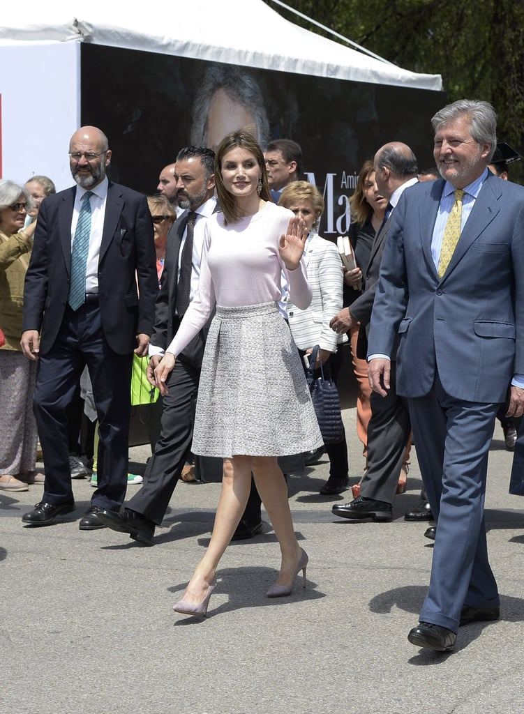 Queen Letizia of Spain knows that, as part of her job, she needs to dress for the occasion. The last month alone has seen her break out an elegant sheath dress for the red carpet at an award show, as well as a more fashion-forward leather pants ensemble for a journalism seminar. Letizia knows that getting dressed is primarily a practical matter —she is, after all, a woman who loves a good outfit repeat.  And on Friday, Letizia hit the sartorial nail on the head once again by selecting a pretty and polished outfit to open the Madrid Book Fair at Retiro Park. The engagement, which took place indoors and outdoors on a lovely Spanish Spring day, called for something elegant but not fussy. Letizia's combination of a simple pink sweater, with a classic tweed-looking skirt and matching suede heels, was a winner. It's an outfit that works in multiple scenarios, as well as on just about everyone —and odds are, you might just have something similar hanging in your own closet.