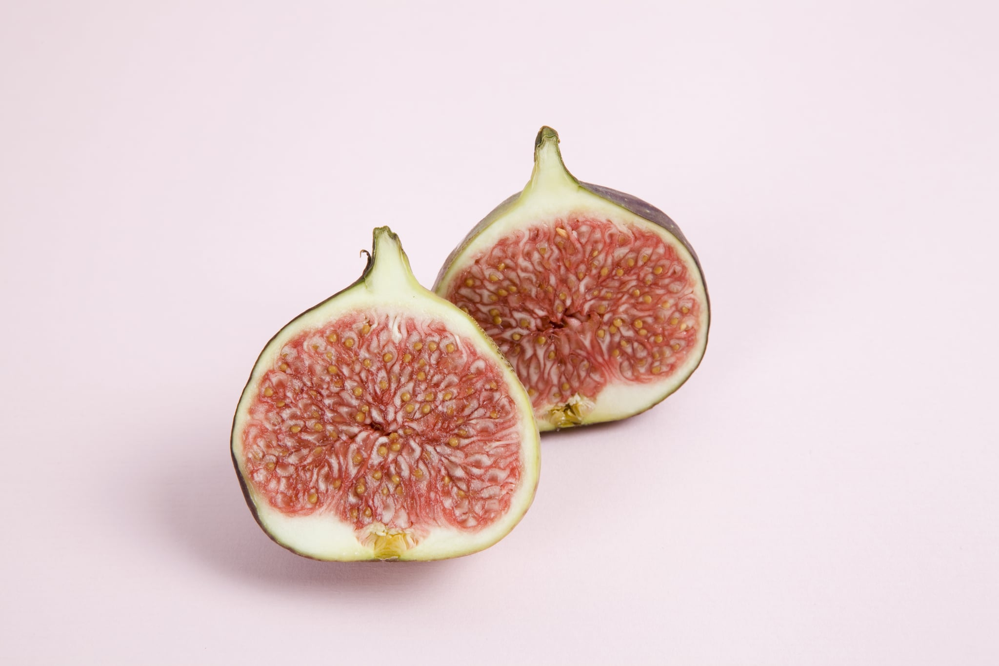 harmony of colors and tones with a fig placed on a pastel pink background. Minimal color still life photography.