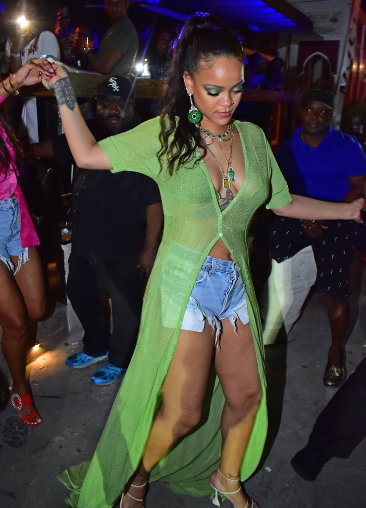 If Summer was a piece of clothing, it'd be Rihanna's sexy sheer sweater dress. The superstar was recently spotted partying at home in Barbados, and she picked a chic beachy look for the occasion. We might reach for slides or even *gasp* flip flops for a summery evening out, but Rihanna doesn't play the same game. Instead, she chose some sexy strappy heels to match her sheer neon green button down and denim shorts. Layered with tons of jewellery and a pop of green eyeshadow, you can bet we're taking notes. Ahead, see more snaps of Rihanna's full outfit, as well as her exact top and shoes.