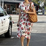 On a coffee run in LA, Eva wore a Free People rose-print dress with wedge sandals, a tan hobo bag, and oversized shades.
