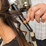 After you've sprayed the hair, wrap the sections of hair around a curling wand. Pipino recommends using a clampless iron, because you get more of a natural wave, as opposed to a polished curl. If you don't have one, you can always wrap your hair around a regular iron, too.