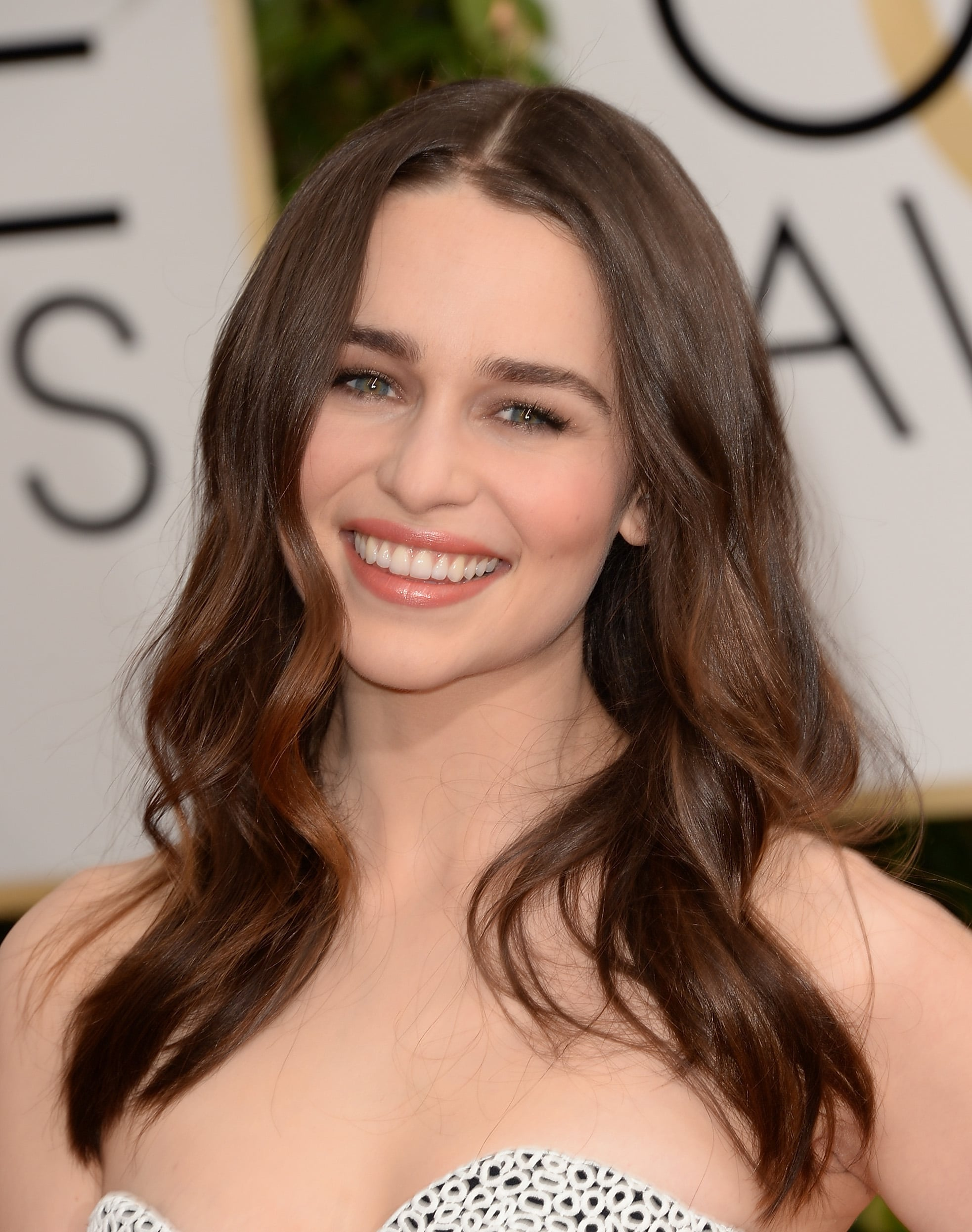 """""""I was so inspired by Emilia's Proenza Schouler gown,"""" Dove celebrity hairstylist Mark Townsend said. """"The mix of embroideries looked like movement, so I wanted her hair to move beautifully as well."""" He prepped her hair adding a few drops of the new Dove Pure Care Dry Oil Nourishing Treatment ($11) in her damp hair and combing it through. Next, he sprayed Dove Oxygen Moisture Root Lift Spray ($6) to the roots and blow-dried strands with a round brush. Then, he took three-inch sections of hair and wrapped each section around a 1.5-inch curling iron, because a larger barrel creates looser waves instead of tight ringlets. He finished the look with Oribe Dry Texturizing Spray ($39) for texture and Dove Pure Care Dry Oil Nourishing Treatment for shine."""