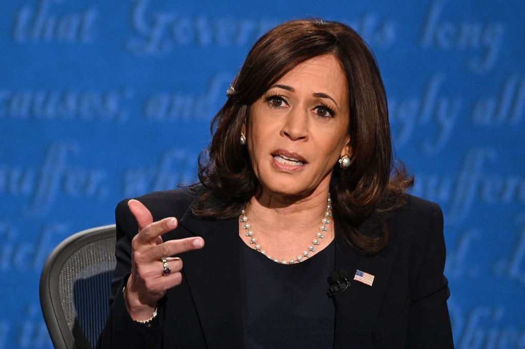 """For one of the most important events of her campaign, Kamala Harris reached for her trusty pearls to face off in the first and only vice presidential debate on Oct. 7. While she kept things simple with her black pantsuit, the senator wore a strand of sparkly pearls with turquoise details and matching earrings, proving once again that she keeps it real when it comes to her looks.  We all know politicians are scrutinized for the messages they convey through their clothing, but Kamala's look isn't complicated. She wears Converse sneakers when she wants to because they're functional and comfortable, and they allow her to move quickly and get sh*t done when she's on the campaign trail. She paints a bold backdrop behind the messages she delivers in her power colors and sensible pearls, too, just because she likes them. Of course, the necklace is timeless, and a sophisticated choice at that, when the majority of Kamala's wardrobe falls into the workwear category.  But Kamala doesn't just stick to one strand of pearls. She has curated an impressive collection over the years — starting with the elegant choker she wore for her Howard University graduation photo in 1986. Kamala has shared this image across her social platforms, causing many people to make the connection to her personal style, and also the sorority she joined, Alpha Kappa Alpha, which is the first Black Greek-letter sorority that refers to its members as the """"Twenty Pearls."""" By making the pearl necklace a seamless part of her uniform, and swapping out her favorite iterations depending on her outfit, she's not just participating in fashion or acknowledging trends, she's both defining her authentic taste and staying true to who she is and the history that's ingrained in her. Kamala clearly treasures her pearls. Most importantly, she wears them in a way that's relatable — throwing them on when they look good and flow with the rest of her ensemble, and not necessarily when they stand out to make an intentional stat"""