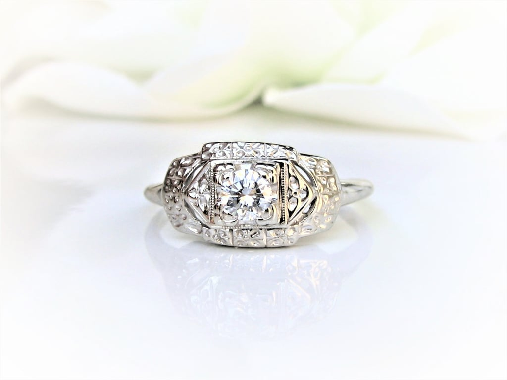 This elegant and detailed art deco engagement ring ($645) features a center diamond and 14k white gold setting with tiny decorative gold orange blossom detailing.