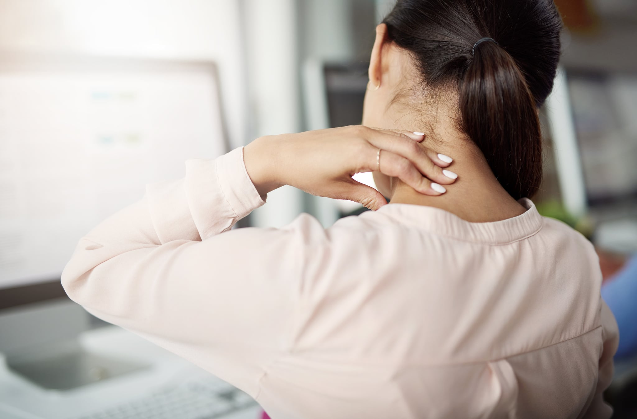 Rearview shot of a young businesswoman experiencing neck pain while working at her desk in a modern office