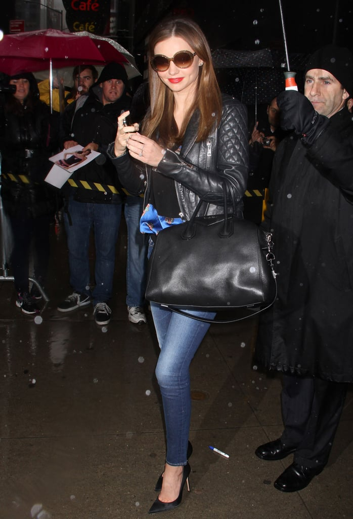 On her way into Good Morning America, Miranda Kerr sported a quilted leather jacket with faded skinny jeans, a printed top, pointy pumps, her Givenchy bag, and oversize round sunglasses.