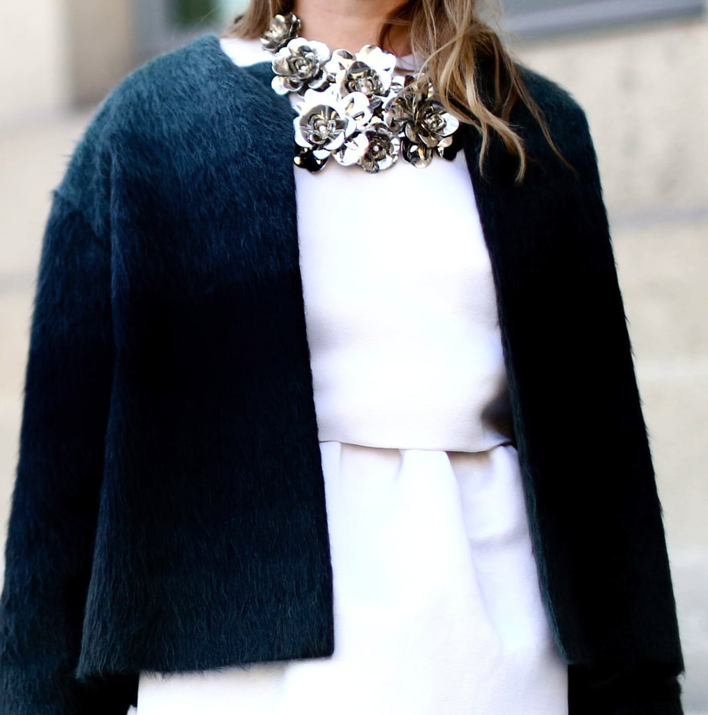 An oversized floral necklace makes a statement against a stark white dress and textural black coat.