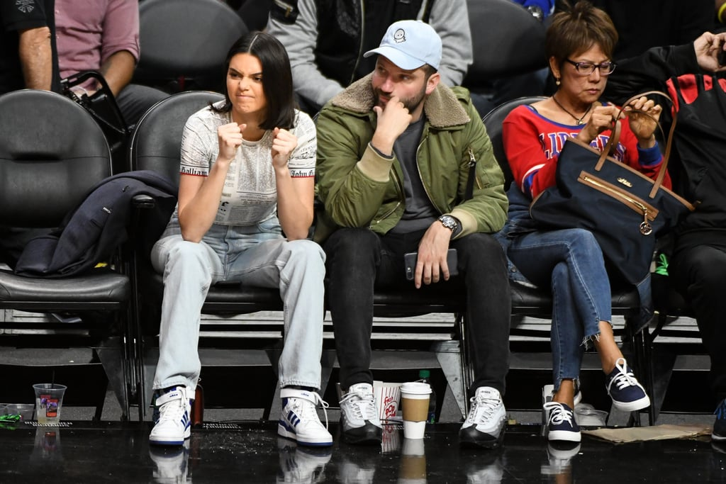 If you want to see what types of shoes are in Kendall Jenner's closet, watch for her at basketball games. Kendall always sits courtside, giving us all a good look at her footwear. She's been spotted in $10,000 Saint Laurent boots, snakeskin booties, and now, a pair of hard-to-find Adidas sneakers (trust us, we've tried). The high-top style featured a Velcro strap in addition to laces, and Adidas's three trademark stripes came in blue to match the sole of the shoes.  The design was more boyish than Kendall's usual go-to kicks, and the rest of her outfit made a statement, too. The star wore a top with newspaper-inspired print and rocked a pair of light-wash denim jeans. She kept her accessories to just a simple pair of hoop earrings, and unlike BFF Bella Hadid, it appears Kendall stayed in the same outfit for the entire Clippers vs. Celtics game. Read on to check out Kendall's cool street wear shoes, then shop similar pairs.