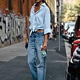 حافظي على بساطة إطلالتكِ ببنطال جينز يعلوه قميص معقود الأزرار ومربوط من الأسفل
