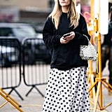 When it's chilly, try layering a sweater over a polka-dot dress.