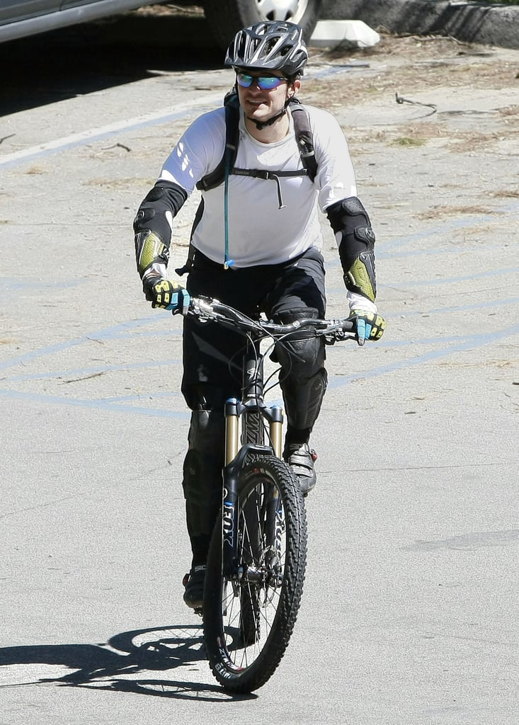 """Orlando Bloom took advantage of the West Coast's sunshine and spent Friday afternoon biking through Pasadena with friends. On Saturday his Three Musketeers costars were a few hundred miles north in San Francisco discussing their Fall blockbuster at WonderCon. Orlando and his wife Miranda Kerr were in the city just one week earlier for an event, but returned to LA where the new mom wowed in a skintight dress on Wednesday. Orlando shows off his swashbuckling skills and outrageous pompadour in the recently released teaser trailer, and according to castmate, Luke Evans, """"sexy hair"""" was rampant on the set. Orlando's locks may once again be the center of attention when he reprises the role of fair-haired Legolas in Peter Jackson's The Hobbit."""