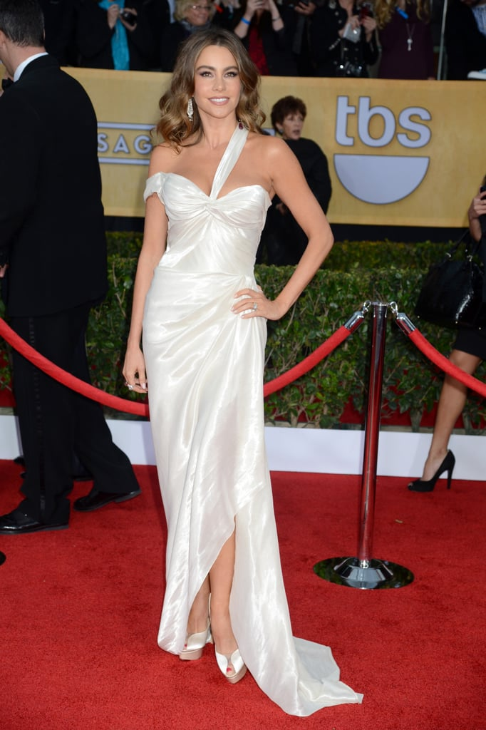 Sofia Vergara hit the red carpet today at the SAG Awards in LA wearing a white Donna Karan gown. It's the latest stunning appearance from Sofia, who wore a black beaded Michael Cinco gown to the Golden Globes earlier this month. This is a big day for her — Sofia's nominated for for outstanding performance by a female actor in a comedy series for her work on Modern Family. Her co-stars Eric Stonestreet and Ty Burrell are both up for outstanding performance by a male actor in a comedy series. The whole cast, meanwhile, is in the running to take home best ensemble in a comedy series. Before we find out if Sofia takes home a trophy, let us know if you think her look is a winner by voting in all of our SAG Awards style polls!
