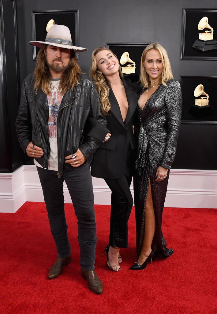 "Miley Cyrus turned the Grammys into a fun family night on Sunday. The ""Nothing Breaks Like a Heart"" singer brought her parents, Tish and Billy Ray Cyrus, as her dates to the award show. Her husband Liam Hemsworth skipped the show after he was reportedly hospitalized on Saturday night. The 26-year-old, who is performing during the show, looked absolutely stunning as she rocked a black pantsuit and flashed the cameras her signature tongue-out pose on the red carpet.   Over the weekend, Miley paid tribute to one very special member of her family: her godmother Dolly Parton. During MusiCares Person of the Year gala on Saturday, Miley and Shawn Mendes gave their own rendition of Dolly and Kenny Roger's 1983 song ""Islands in the Stream."" And during the show, Miley shared even more sweet moments with Dolly as they shared the stage for the country singer's star-studded tribute.       Related:                                                                                                           We Can't Get Enough of Miley Cyrus and Her Famous Family"