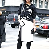 This show-goer kept the color story going on black and white sweatshirt, black-trimmed white pencil skirt, black tights, and white pumps. This is a full commitment to the trend.