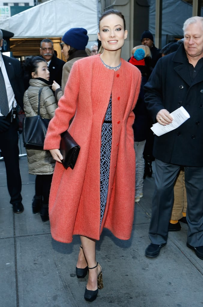 She topped her detailed dress with a punchy orange coat.