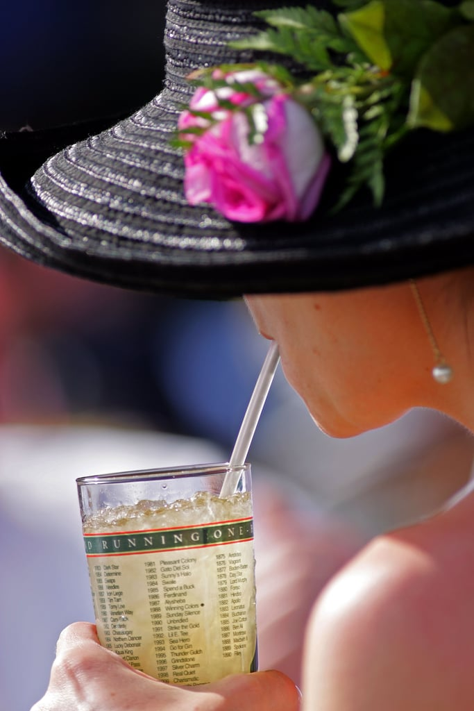 A fan drank a mint julep under her pink and black hat in 2006.