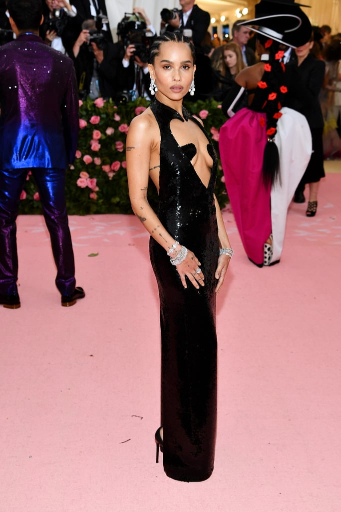 """Zoë Kravitz could major in sexy Met Gala dresses, with her flawless track record. The Big Little Lies actress arrived at The Metropolitan Museum of Art in NYC on May 6, all dressed up in a sultry, eye-catching Saint Laurent number.  The all-black sequined gown might appear demure from the back, but the front is all about the skin-baring cutouts. Zoë tied the look together with dangling statement pearl earrings and layered silver bracelets, letting the dress do most of the talking. While her look was definitely subtler than some of the other """"Camp: Notes on Fashion""""-themed looks we've seen, it certainly added some heat to the red carpet. Keep reading to see more angles of Zoë's daring choice ahead."""
