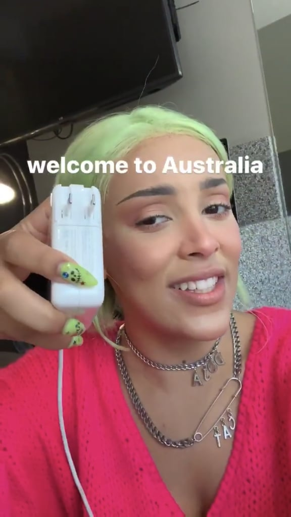 While Doja Cat was hilariously freaking out on her Instagram Story about Australian electrical plugs, we couldn't help but notice she might be taking beauty notes from Billie Eilish. Over the Summer, Eilish went all-in on neon green, wearing the color on her nails and in her hair. Doja Cat seems to be following her lead, because she coordinated her neon green hair with almond-shaped nails in the Instagram video. She's always playful with her beauty look, and we especially love the creepy-cute smiley nail art on her manicure. Doja Cat often switches up her hair color so it's possible that her vibrant hair is a wig, making her pairing even more intentional. Check out her neon green beauty look, ahead.