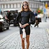 Style a billowy minidress with black boots and a chic white bag.