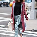 Amal mixed and matched patterns in her outfit while out and about in NYC in 2016. She wore a black sweater with a printed red coat, gingham-print trousers, and black pumps.