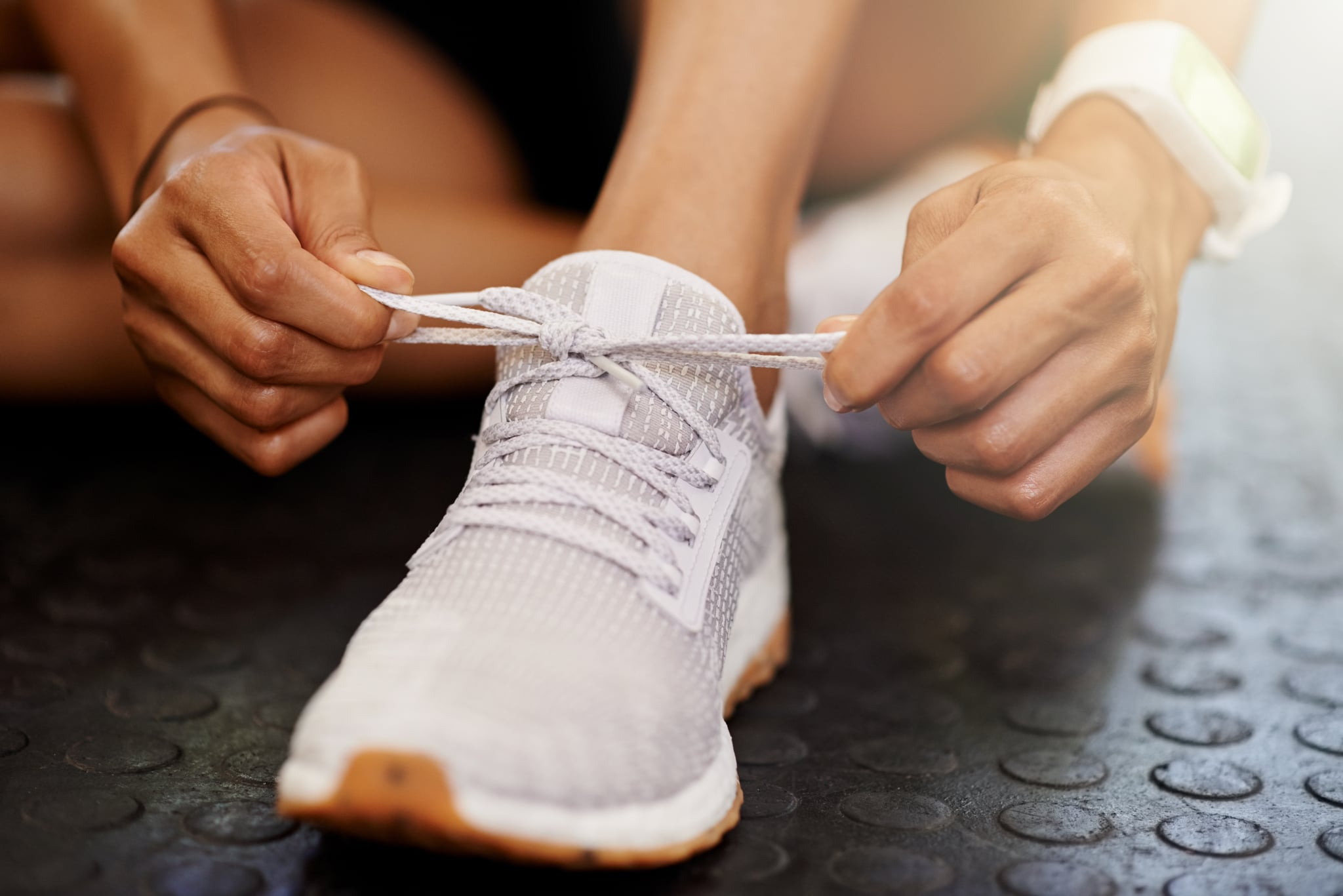 Cropped shot of a woman tying the shoelaces of her sports shoe