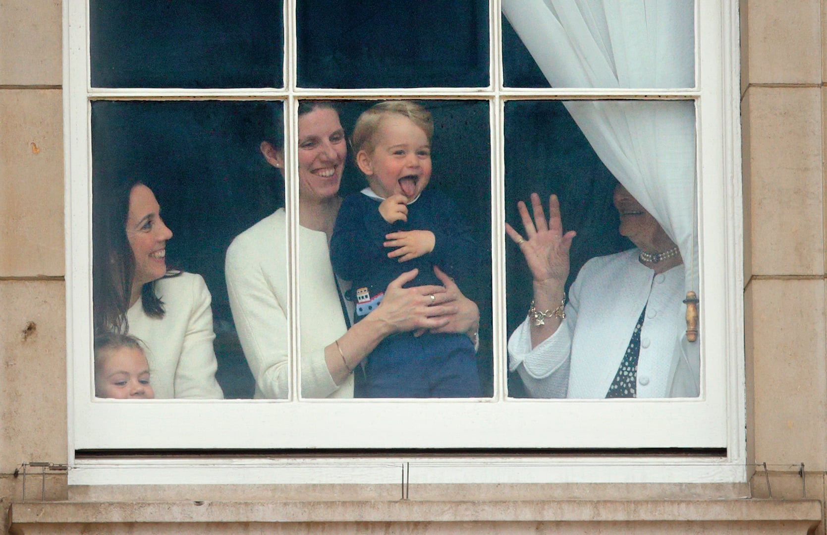 LONDON, UNITED KINGDOM - JUNE 13: (EMBARGOED FOR PUBLICATION IN UK NEWSPAPERS UNTIL 48 HOURS AFTER CREATE DATE AND TIME) Prince George of Cambridge being held up at a window of Buckingham Palace by his nanny  Maria Teresa Turrion Borrallo to watch Trooping the Colour on June 13, 2015 in London, England. The ceremony is Queen Elizabeth II's annual birthday parade and dates back to the time of Charles II in the 17th Century, when the Colours of a regiment were used as a rallying point in battle. (Photo by Max Mumby/Indigo/Getty Images)