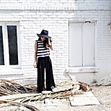 A Striped Tank Top, Black Wide-Leg Trousers, and a Hat