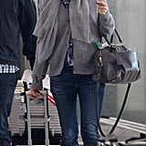 Gwyneth Paltrow wore a gray scarf and black boots as she touched down in London.