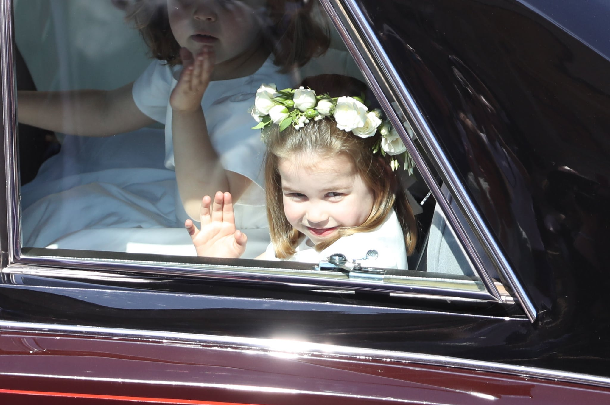 WINDSOR, ENGLAND - MAY 19:  Princess Charlotte waves to the crowd as she rides in a car to the wedding of Prince Harry and Meghan Markle at St George's Chapel in Windsor Castle on May 19, 2018 in Windsor, England.  (Photo by Andrew Milligan - WPA/Getty Images)