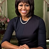 For her (updated) White House official portrait, Michelle chose a customized navy blue Reed Krakoff sheath, and paired it with a single strand of pearls.