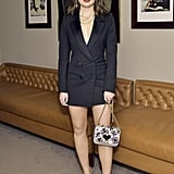 At a dinner wearing a black blazer dress with a Kate Spade bag.
