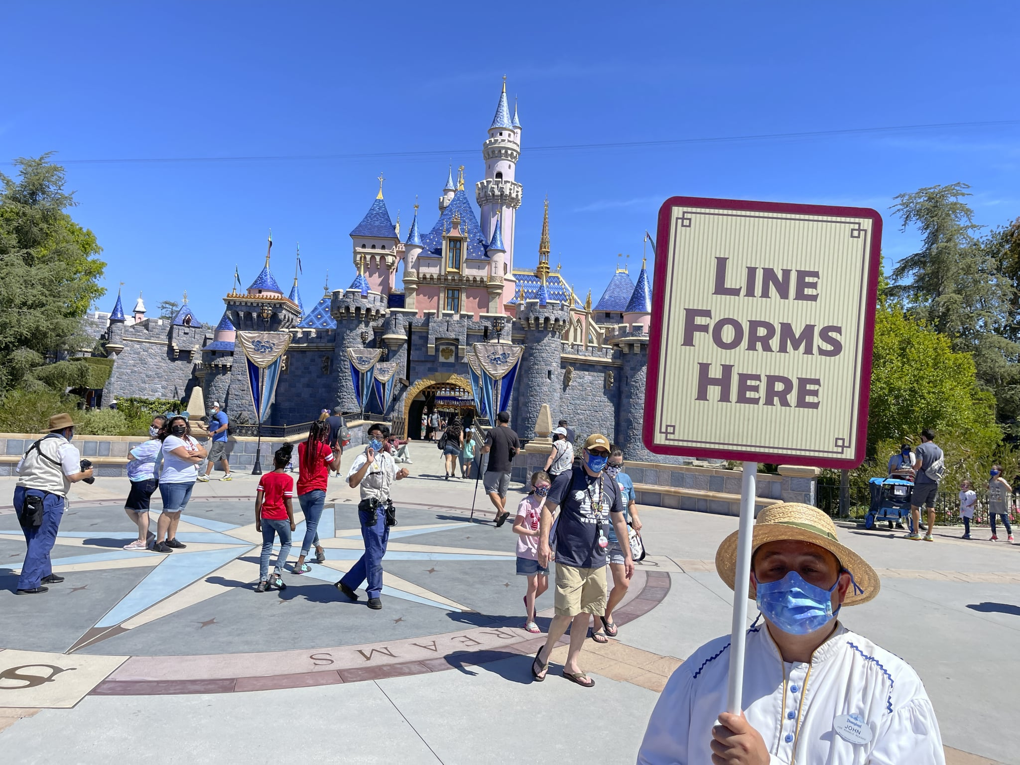 Anaheim, CA - April 30: A Disneyland employee forms a line for visitors to take pictures in front of Sleeping Beauty Castle in Anaheim, CA, on Friday, April 30, 2021. The resort