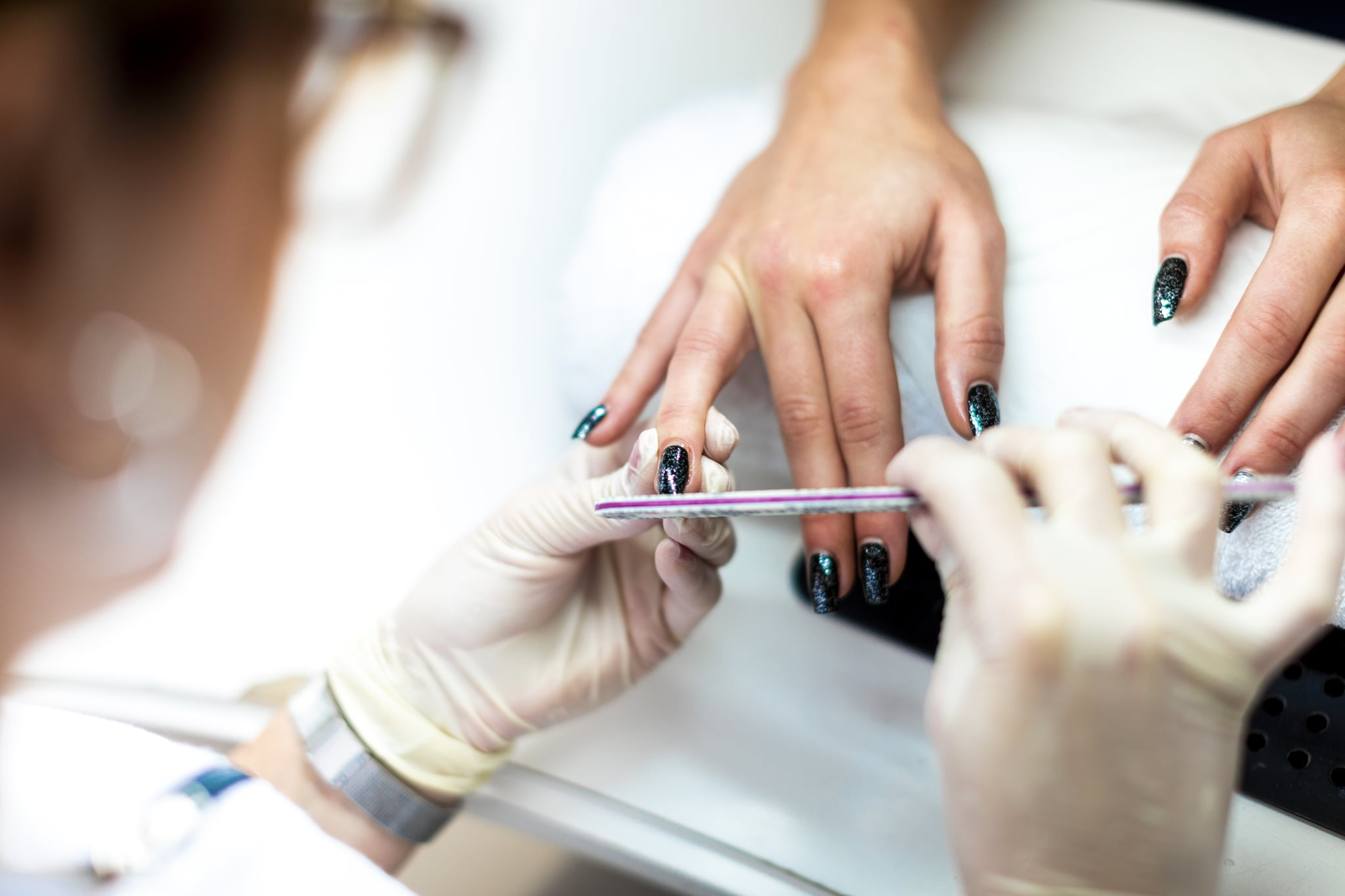 A nail file being used to tidy up a nail and remove cuticles during a manicure procedure.