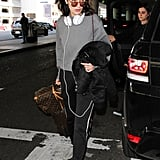 Playing up the gray shade of her sweatshirt with Yeezy sneakers and toting her Louis Vuitton luggage at her side.