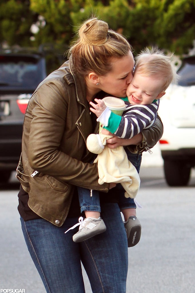 "Hilary Duff planted a big kiss on her little boy Luca Comrie's cheek on Sunday as she carried him into a Bristol Farms grocery store in LA. The affectionate mom and her hockey-player husband, Mike Comrie, stopped in to go shopping before celebrating their third holiday as a married couple and their first with baby Luca. Hilary paired a brown leather jacket with black booties and a high bun, while a giggling Luca sported stripes and a pair of baby New Balance shoes. Hilary and Mike may be done having kids, according to a recent statement the mother of one made about their ""perfect"" little guy, but she still had plenty of holiday love to share. Hilary tweeted, ""Happy Christmas Eve! Sending love and merry thoughts to everyone today! Big hugs and kisses!"""