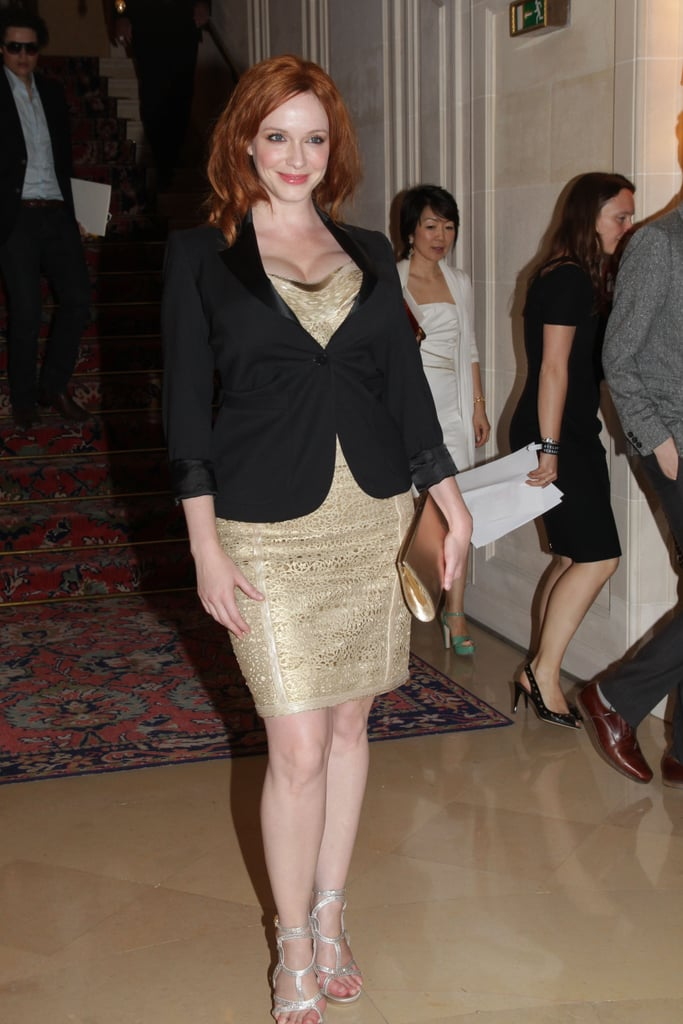 Christina Hendricks wore a gold dress with a black blazer to the Versace show for Paris Fashion Week.