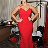 Posing backstage in a stunning red gown by Christian Siriano.