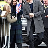 When in Edinburgh, he wore a gray coat, a navy sweater, a white shirt, and black pants.