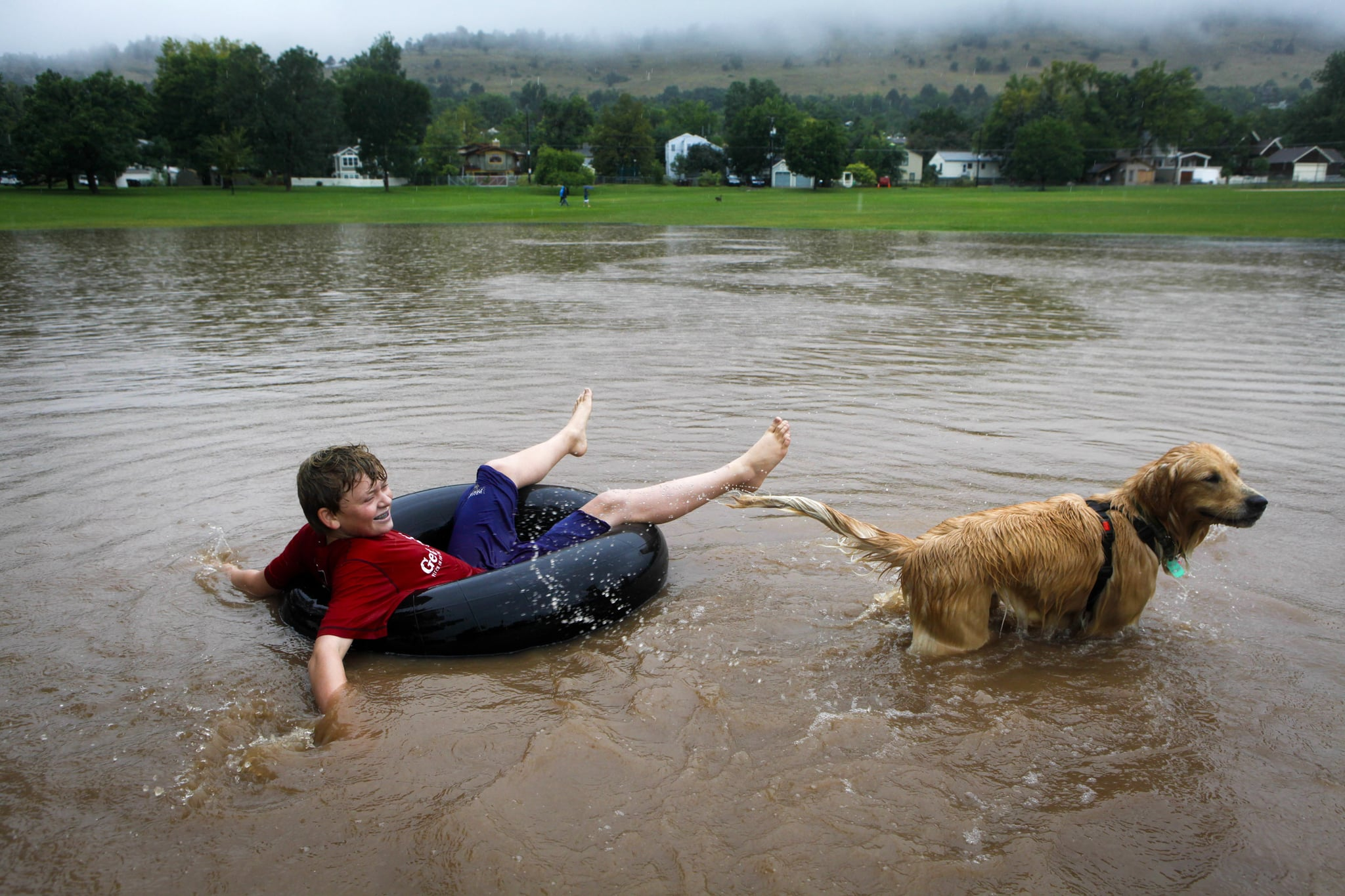 A boy floated through the flood waters with a dog.
