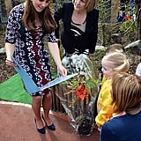 Kate Middleton received a giant book from schoolchildren at the Willows Primary School in Manchester, England. She showed off her growing baby bump in a printed dress during the April trip.