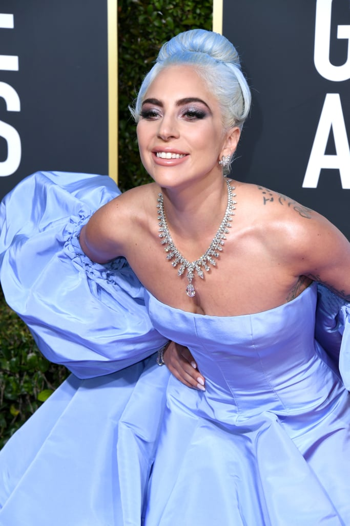 "Lady Gaga's outfit at the 2019 Golden Globes was more than just a gorgeous gown. The singer and actress wore a periwinkle Valentino Couture dress reminiscent of one worn by Judy Garland in the 1954 adaptation of A Star Is Born. In addition to the shade of purple, the voluminous sleeves are undeniably similar. The meaningful red carpet moment only added to the many ways Gaga and Bradley Cooper paid tribute to the previous A Star Is Born films that came before their version. Gaga is nominated for best actress in a drama at the award ceremony. Judy's performance also earned her a nomination for best actress in a motion picture comedy or musical, which she won. Judy would go on to also earn a best actress nomination at the Academy Awards, and it's very likely Gaga will soon receive the same. See pictures of Gaga's sartorial salute to Judy ahead.      Related:                                                                                                           These Golden Globes Red Carpet Looks Scream ""Let's Get This Party Started!"""
