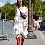 Wear a cherry red cowboy boot with a romantic, tiered knee-length dress.