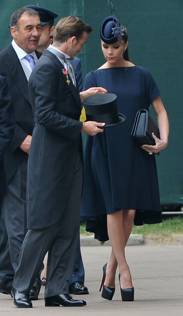 David Beckham in Ralph Lauren Purple Label and Philip Treacy top hat, and Victoria Beckham in a modified version of Look #2 from her Fall 2011 collection, Philip Treacy hat, and custom Christian Louboutin shoes
