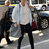 Olivia Munn added interest to her black and white airport ensemble with a chambray shirt and a gray studded shoulder bag.