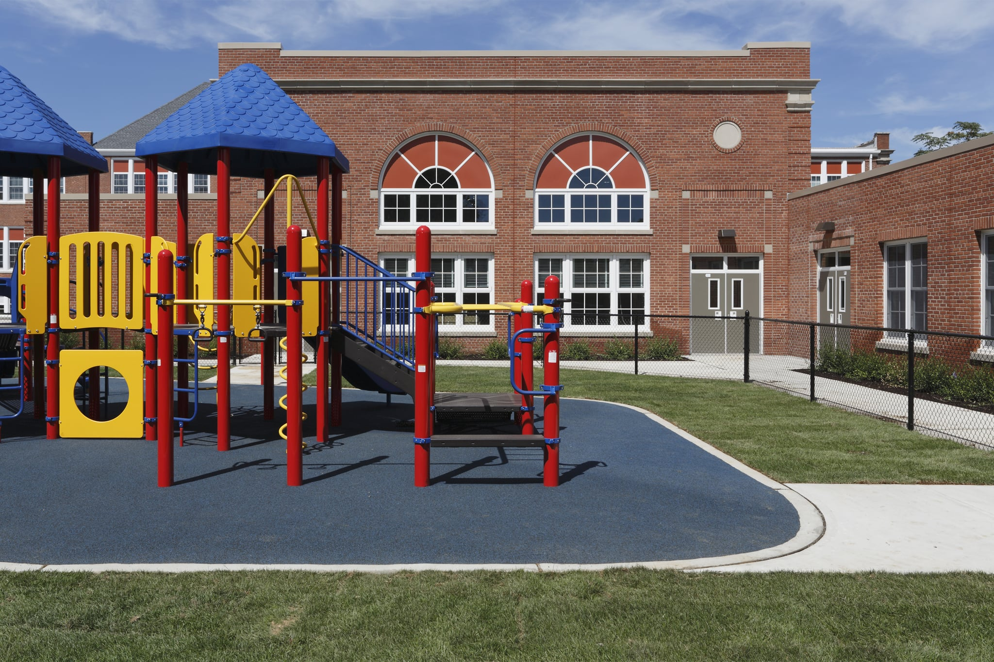 gated elementary school playground with colourful jungle gym equipment, slides, monkey bars, mazes, on padded play surface, with large brick school building complex