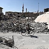 A boy rides his bike amidst the rubble in rebel-held Douma outside of Damascus.