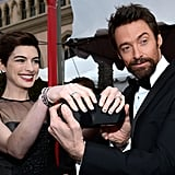 Hugh Jackman helped Anne Hathaway show off her clutch on the SAGs red carpet.